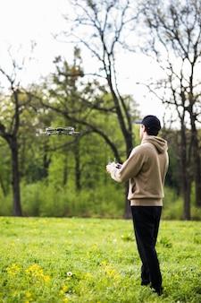 Młody człowiek obsługujący drona z pilotem na zewnątrz