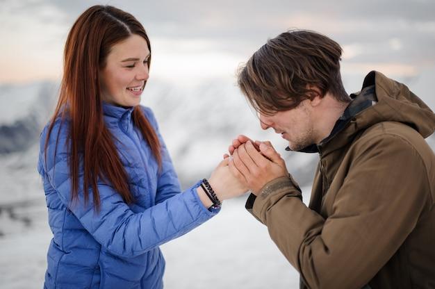 Młody człowiek ocieplenie jego ręce dziewczyny z oddychaniem w górach