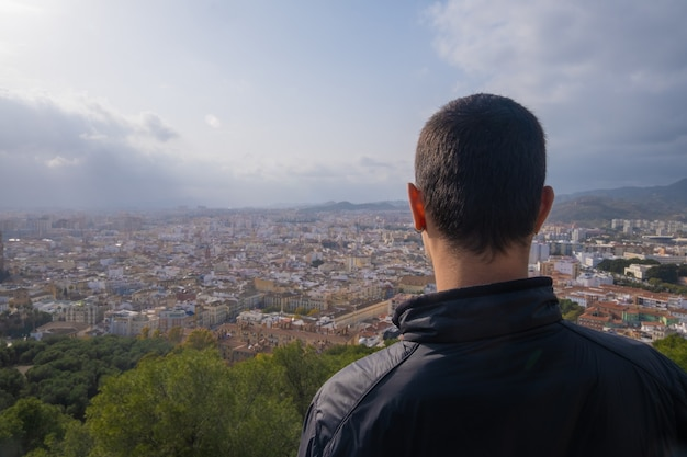 Młody człowiek od tyłu patrząc na miasto malaga.