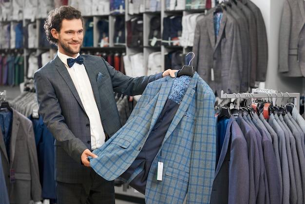 Młody człowiek odbiera garnitur w sklepie.