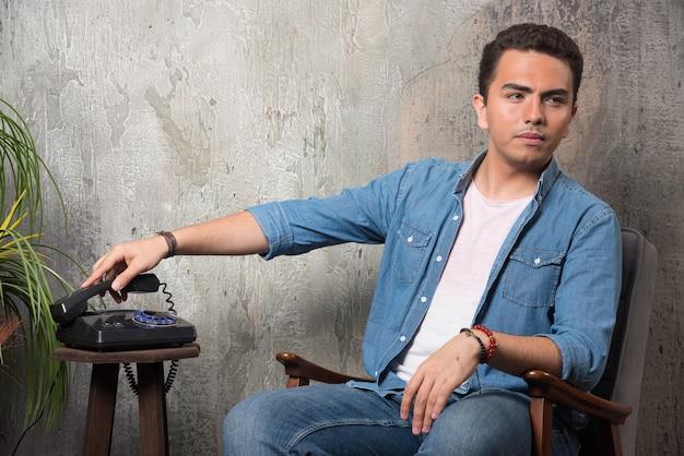 Młody człowiek oddanie słuchawki i siedzi na krześle. wysokiej jakości zdjęcie