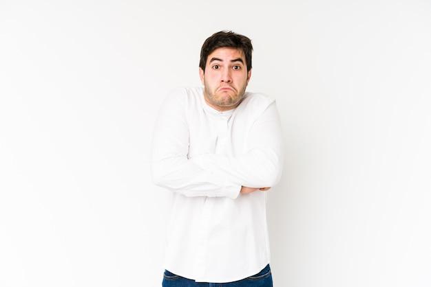 Młody człowiek odizolowywający na bielu wzrusza ramionami ramiona i opon oczy zmieszani.