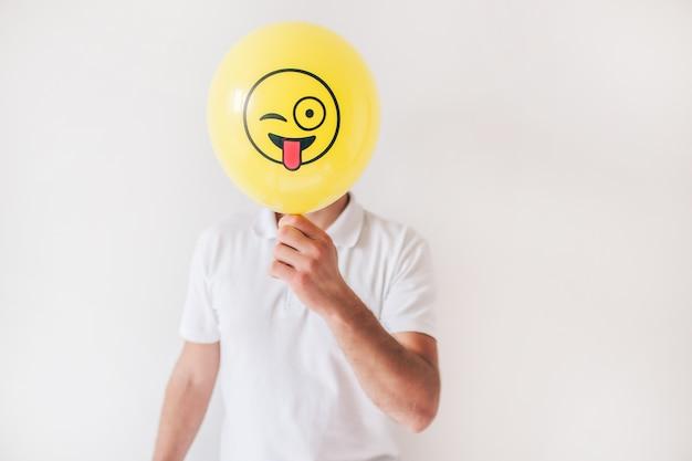 Młody człowiek odizolowywający nad biel ścianą. facet w koszuli trzymać żółty balon z przodu twarzy. malowane emoji z językiem na zewnątrz. ukryj lub zakryj twarz.