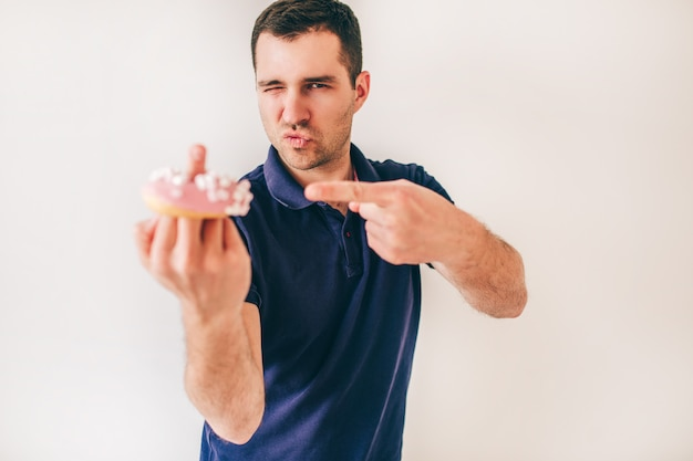 Młody człowiek odizolowywający nad biel ścianą. niegrzeczny facet trzyma pączek na jednym palcu i pokazuje kurwa znak. dwa palce razem na drugiej ręce.