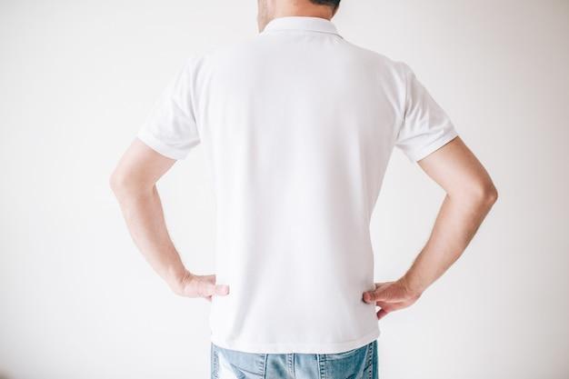 Młody człowiek odizolowywający nad biel ścianą. odciąć widok faceta, trzymając się za ręce na biodrach.