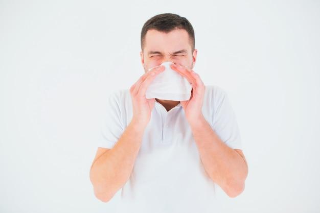 Młody człowiek odizolowywający nad biel ścianą. zakryj nos białą chusteczką. chory i chory kicha do białej serwetki.