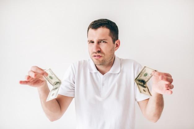 Młody człowiek odizolowywający nad biel ścianą. zmieszany facet trzyma w rękach dwa sto dolarów rachunków.