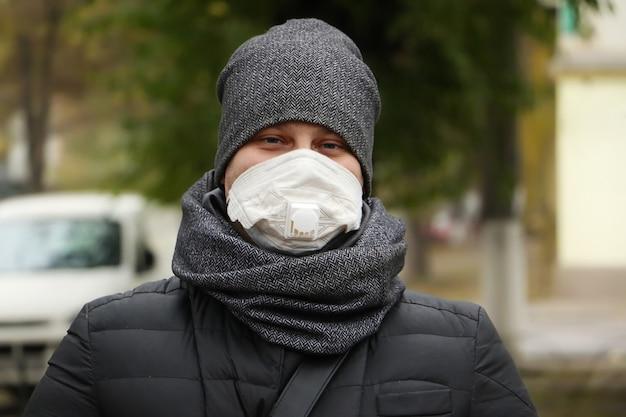 Młody człowiek odkryty w białej masce medycznej z respirator.concept ochrony zdrowia przed covid i innymi chorobami.