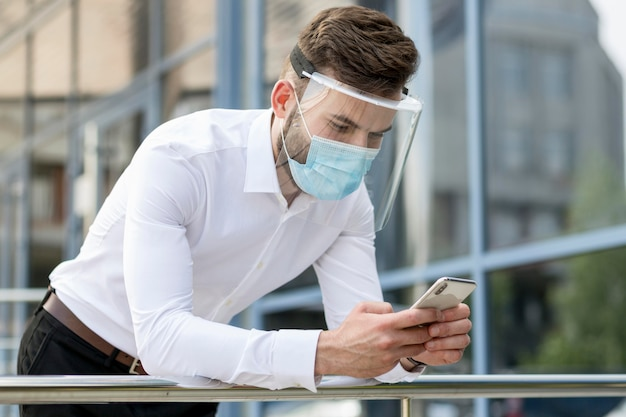 Młody człowiek odkryty z maską sprawdzanie telefonu komórkowego