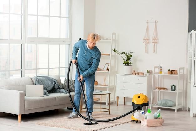 Młody człowiek odkurzanie dywanu w domu