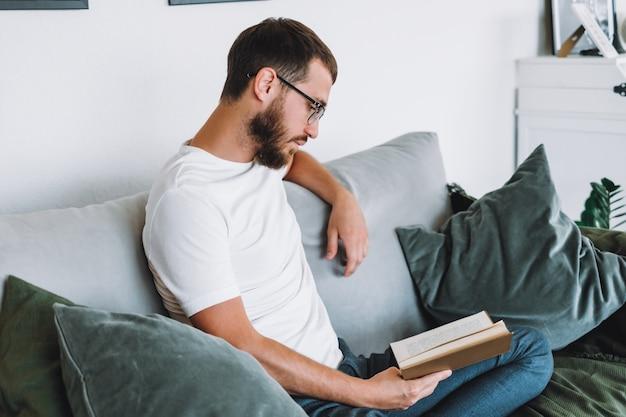 Młody człowiek odpoczywa na kanapie i czyta książkę