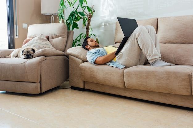Młody człowiek odpoczywa na kanapie w domu i używa laptopa z psem obok niego