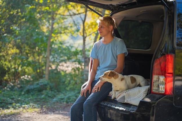 Młody człowiek odpoczywa na łonie natury z samochodem terenowym i psem jack russell terrier. baw się i ciesz się wakacjami