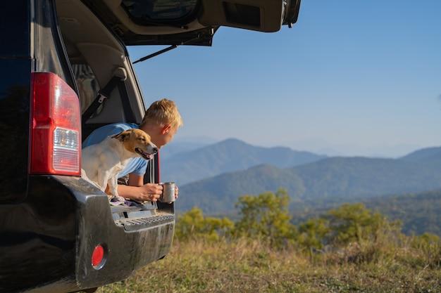 Młody człowiek odpoczywa na łonie natury z samochodem terenowym i psem jack russell terrier. pije kawę z podróżnego żelaznego kubka