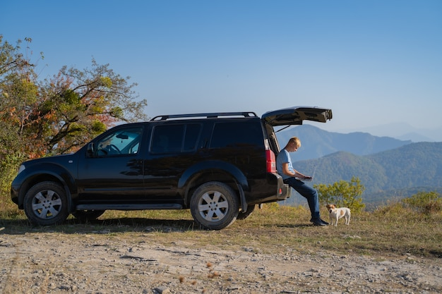 Młody człowiek odpoczywa na łonie natury z samochodem terenowym i psem jack russell terrier. używa laptopa do czatowania w internecie