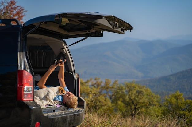 Młody człowiek odpoczywa na łonie natury z samochodem terenowym i psem jack russell terrier. używa telefonu komórkowego do komunikacji mobilnej i internetu.