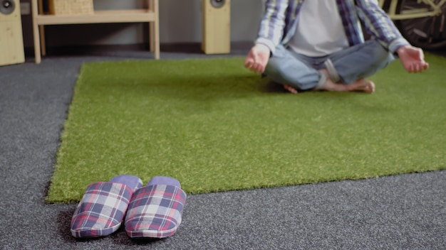 Młody człowiek odpoczywa na zielonym dywanie