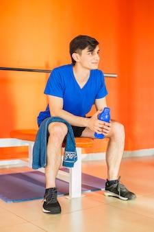 Młody człowiek odpoczywa po treningu na siłowni