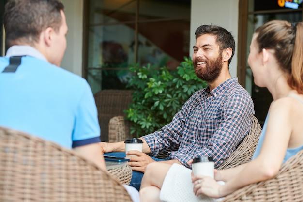 Młody człowiek odpoczywa z przyjaciółmi w kawiarni