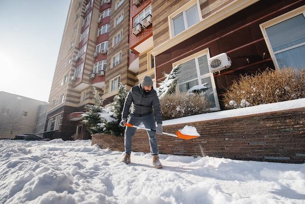 Młody człowiek odśnieża przed domem w słoneczny i mroźny dzień. czyszczenie ulicy ze śniegu.