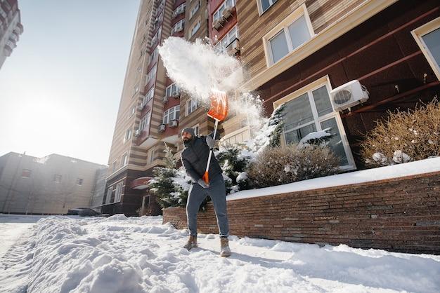 Młody człowiek odśnieża przed domem w słoneczny i mroźny dzień. oczyszczanie ulicy ze śniegu.