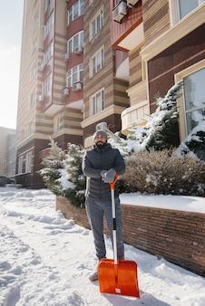 Młody człowiek odśnieża przed domem w słoneczny i mroźny dzień.