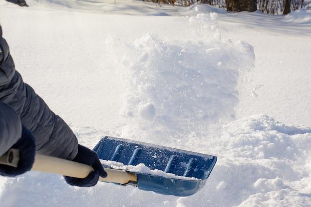 Młody człowiek odśnieżasz śnieg po śnieżycy w słoneczny poranek