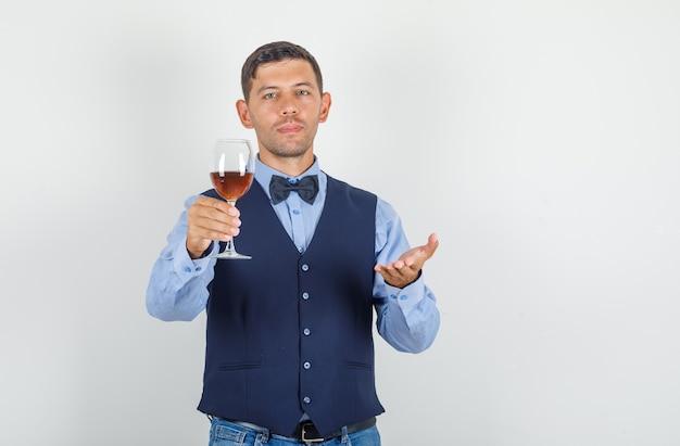 Młody człowiek oferuje napój alkoholowy w garniturze, dżinsy