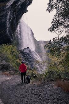 Młody człowiek ogląda duży wodospad obok swojego psa labrador.