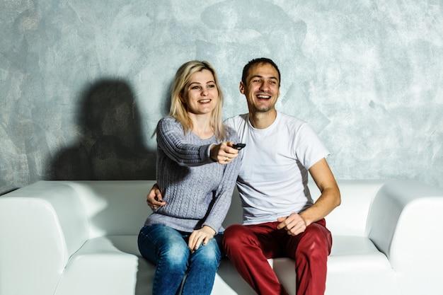 Młody człowiek ogląda futbol z jego żoną w domu