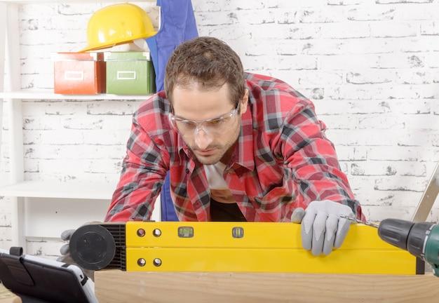 Młody człowiek ogląda poziomicę, aby odczytać pozycję bańki, aby zapewnić poziomą linię