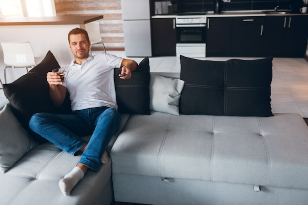 Młody człowiek ogląda telewizję we własnym mieszkaniu. facet siedzi na kanapie i ogląda telewizję z kieliszkiem alkoholu w ręku.
