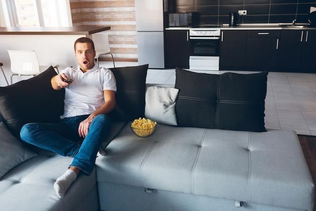 Młody człowiek ogląda telewizję we własnym mieszkaniu. niezadowolony emocjonalny facet siedzi na kanapie i używa pilota do zmiany kanałów. zaskoczony nieoczekiwany program. usiądź sam w pokoju. światło dzienne.