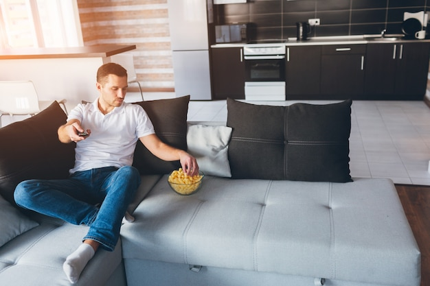 Młody człowiek ogląda telewizję we własnym mieszkaniu. poważny, skoncentrowany facet trzyma w ręku pilota i bierze przekąskę z miski. oglądaj film lub telewizję w pokoju sam. spokojny spokojny zwykły facet na zdjęciu.