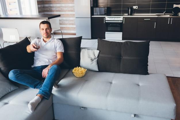 Młody człowiek ogląda telewizję we własnym mieszkaniu. radosny szczęśliwy atrakcyjny zwykły facet trzyma pilota z wyprostowaną ręką. przełączanie kanałów telewizyjnych. baw się w domu.