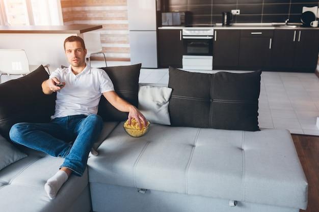Młody człowiek ogląda telewizję we własnym mieszkaniu. szczęśliwy, radosny, spokojny facet bierze przekąskę z miski i używa pilota w dłoni. oglądaj telewizję lub film sam w pokoju. movieholic.
