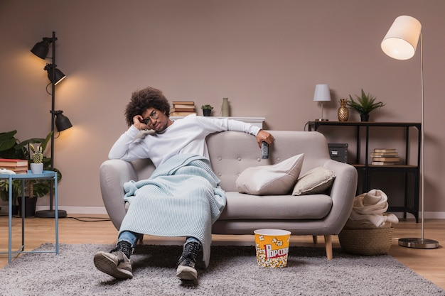 Młody człowiek ogląda tv w domu