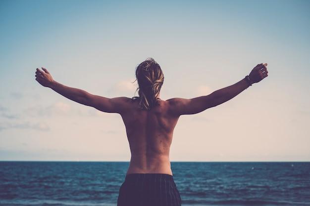Młody człowiek oglądany z tylnych ramion i przytulający wodny ocean raj przed nim cieszący się wolnością i wakacyjnymi podróżami żądnymi emocjami