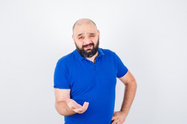 Młody człowiek omawiając coś pokazując gesty rąk w niebieskiej koszuli i patrząc skupiony. przedni widok.