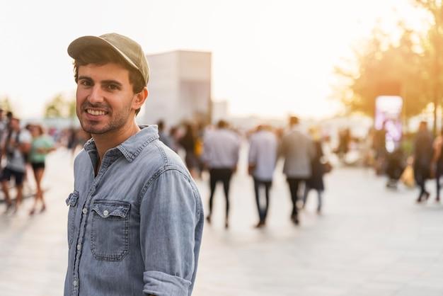 Młody człowiek ono uśmiecha się na ulicie z koszula
