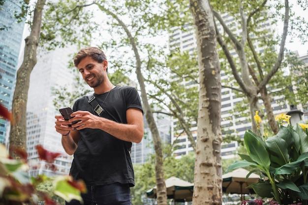 Młody człowiek ono uśmiecha się podczas gdy patrzejący ekran telefonu