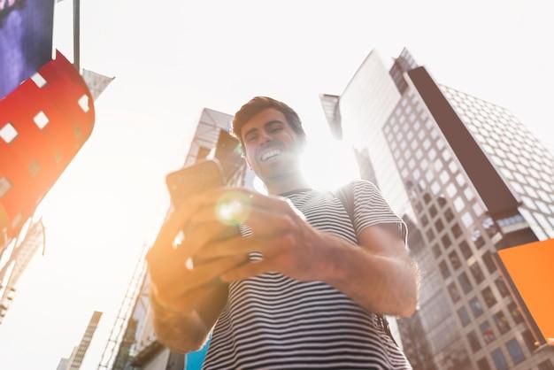 Młody człowiek ono uśmiecha się podczas gdy używać jego smartphone
