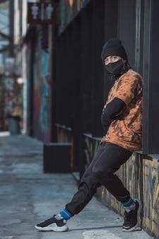 Młody człowiek oparty na ścianie i ubrany w czarną maskę i kapelusz