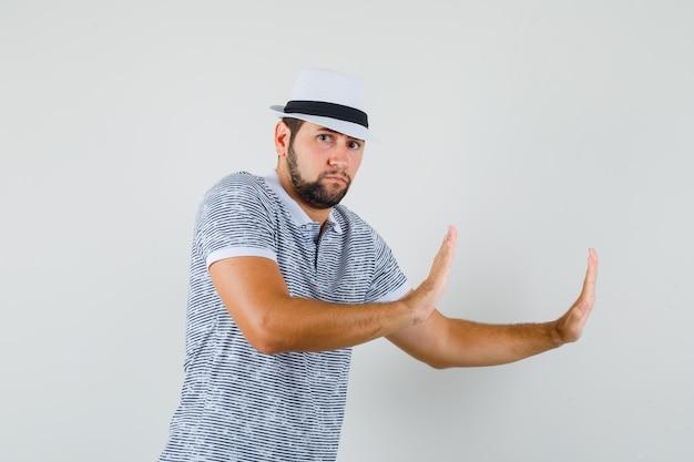Młody człowiek opierając ręce o ścianę w t-shirt w paski, kapelusz i patrząc skoncentrowany, widok z przodu.