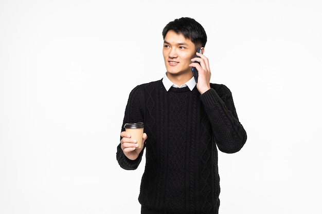 Młody człowiek opowiada na telefonie komórkowym z kawą na biel ścianie