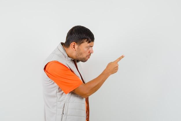 Młody człowiek ostrzegający kogoś palcem w koszulce, marynarce i wyglądający na zdenerwowanego. .