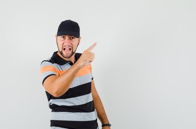 Młody człowiek ostrzeżenie z palcem w koszulce, czapce i patrząc nerwowo.