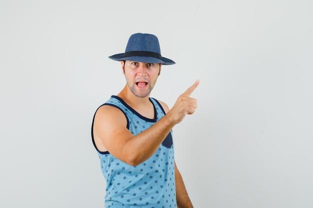 Młody człowiek ostrzeżenie z palcem w niebieskim podkoszulku, kapeluszu i zły wygląd. przedni widok.