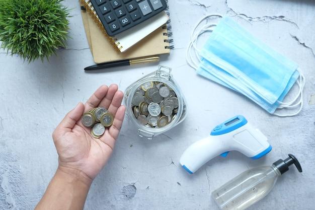 Młody człowiek oszczędzający monety w słoiku z maską na twarz i środkiem dezynfekującym do rąk na stole