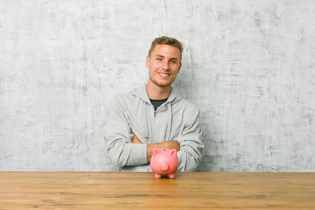 Młody człowiek oszczędzający pieniądze z skarbonką, która czuje się pewnie, krzyżując ręce z determinacją